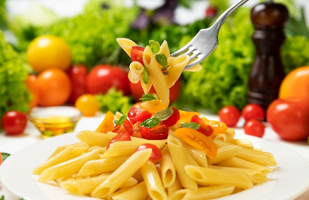 Тарелка приготовленных итальянских макарон, пенне ригате на вилке с помидорами и листьями базилика