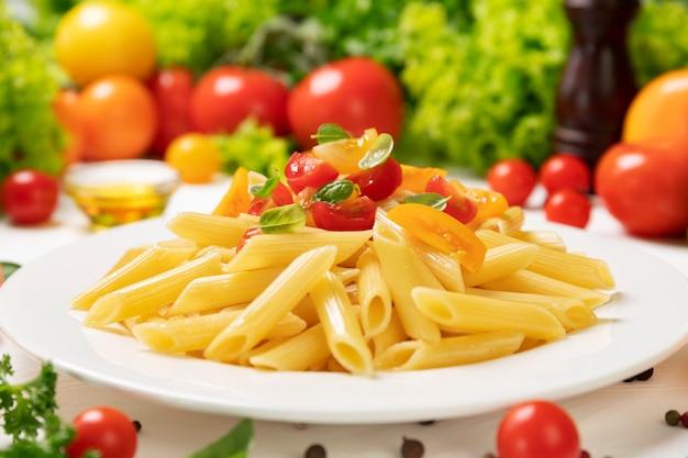 Тарелка приготовленной итальянской пасты, пенне ригате с помидорами и листьями базилика