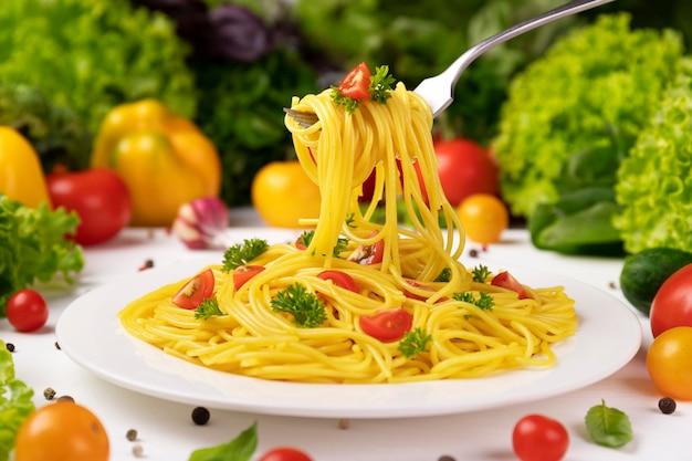 Тарелка приготовленной итальянской пасты, спагетти на вилке с помидорами и листьями базилика