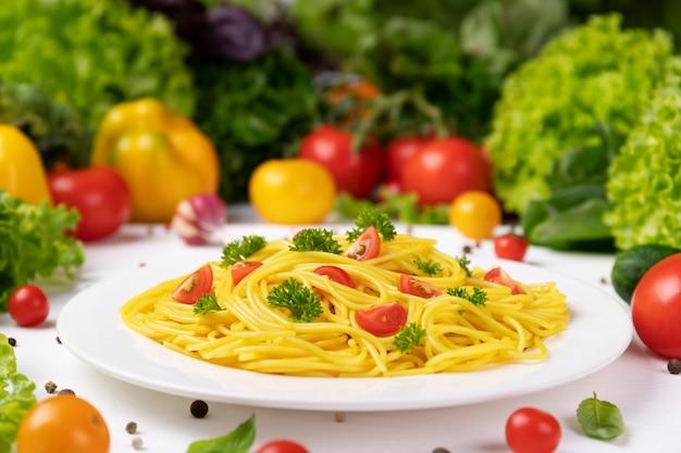 Тарелка приготовленной итальянской пасты, спагетти с помидорами и листьями базилика
