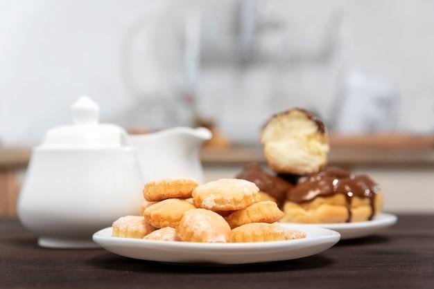 クッキーとエクレアのプレート、シュガーボウル。甘いデザート。お茶を焼く