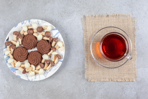 대리석 백그라운드에 차 한 잔 옆에 초콜릿 버섯과 쿠키 접시. 고품질 사진