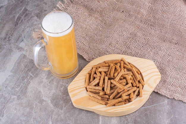 Тарелка крекеров с пивом на мраморной поверхности. фото высокого качества