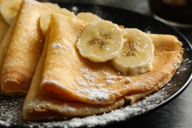 설탕 가루와 바나나 크레페 접시를 닫습니다.