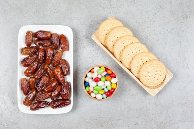 Тарелка фиников рядом с миской конфет и печенья на деревянном подносе на мраморном фоне. фото высокого качества
