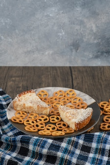 나무 테이블에 소금에 절인 프레즐과 맛있는 케이크 조각 접시.