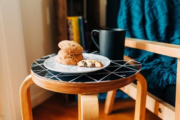 コーヒーハウスの黒いテーブルの上のコーヒーの黒いマグカップの横にあるおいしいクッキーのプレート