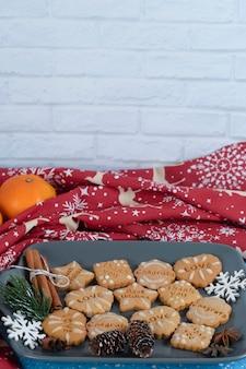 青い背景においしいジンジャーブレッドクッキーとみかんのプレート。高品質の写真