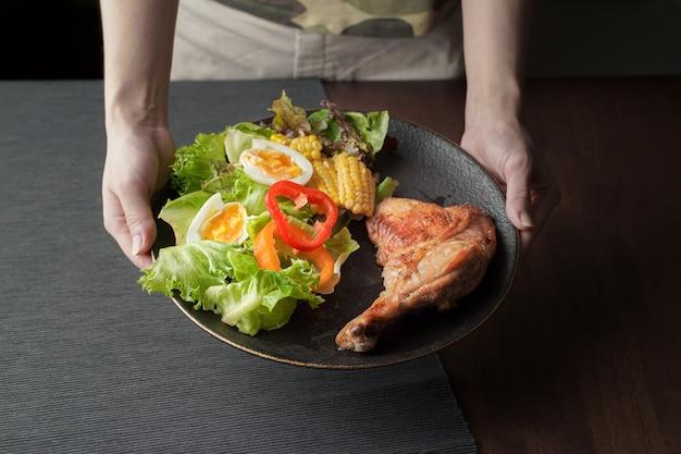 나무 테이블에 야채 샐러드와 함께 맛있는 구운 닭 다리 스테이크 접시