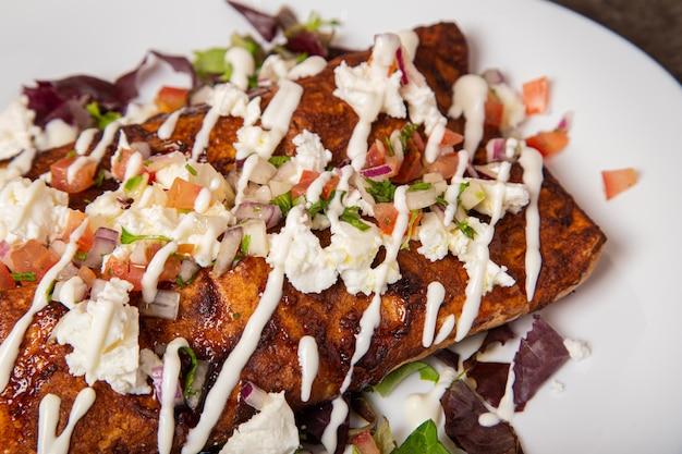 Тарелка вкусной мексиканской куриной энчилада с моль соусом и плавленым сыром