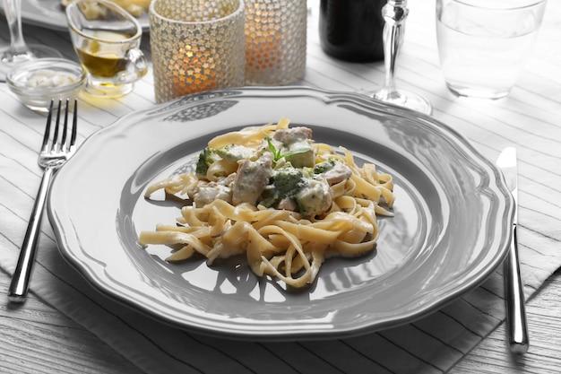 Тарелка вкусной пасты альфредо с курицей на сервированном столе