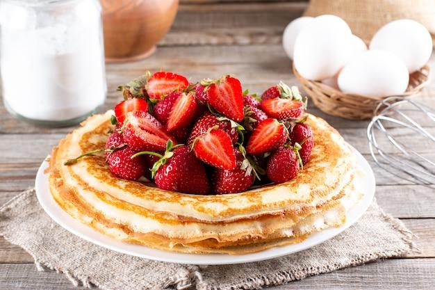 나무 테이블에 딸기가 있는 맛있는 얇은 팬케이크 접시