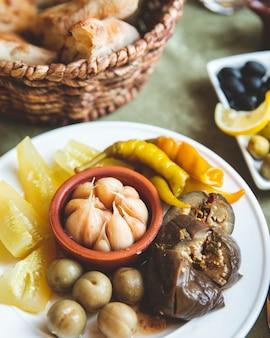 Тарелка разных солений баклажаны чеснок огурцы и перец