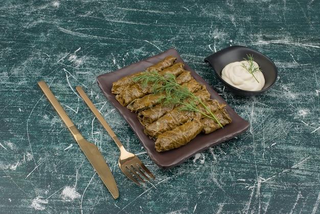 돌마와 대리석 벽에 사워 크림의 접시.
