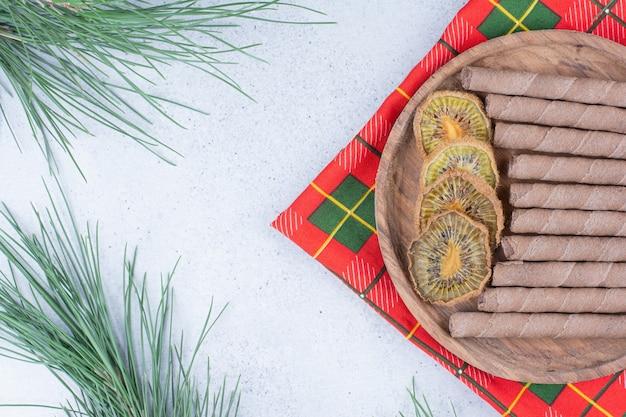 乾燥したキウイスライスのプレートとテーブルクロスにビスケットを貼り付けます。