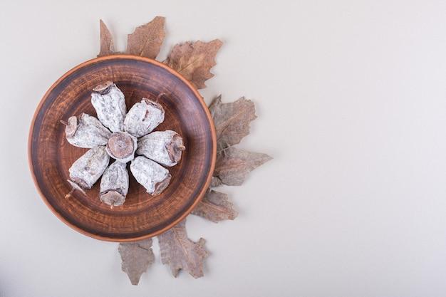 白い背景の上の干し柿と乾燥した葉のプレート。高品質の写真