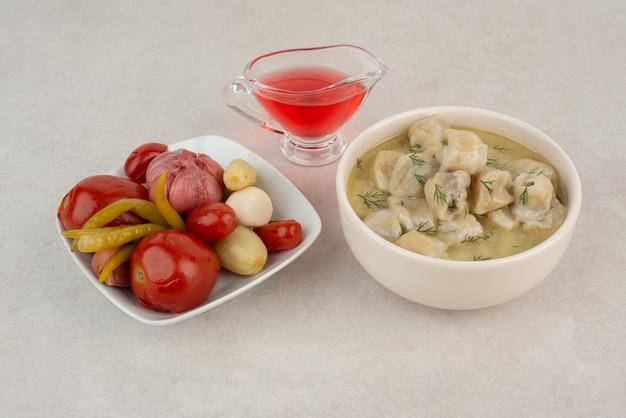 Тарелка пельменей и соленых овощей на белом столе.