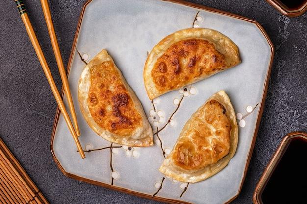 Тарелка пельменей закуски с палочками для еды