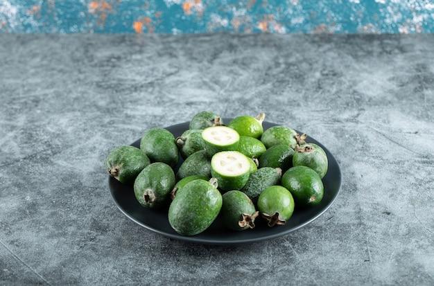 대리석 테이블에 feijoa 과일 접시입니다. 고품질 사진