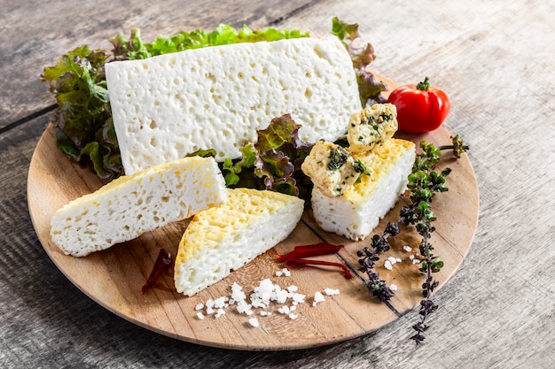 Тарелка с сыром фета с зеленью и специями на деревенский деревянный столик