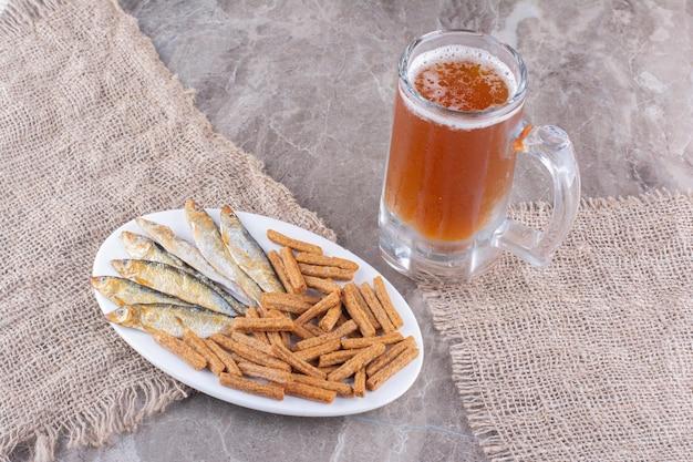 Тарелка рыбы и крекеров с пивом на мраморной поверхности. фото высокого качества