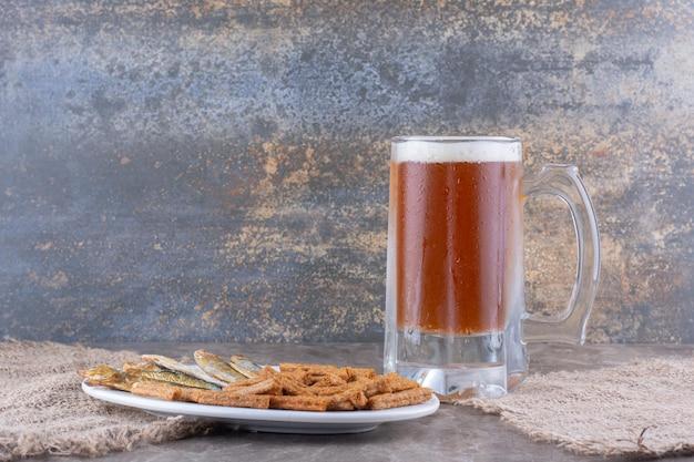 Тарелка рыбы и крекеров с пивом на мраморном столе. фото высокого качества