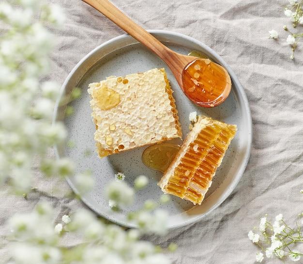 灰色のリネン生地の背景、上面図に新鮮な蜂蜜の櫛のプレート