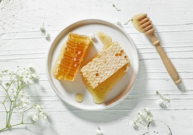 흰색 나무 테이블에 신선한 꿀 빗 접시, 위쪽