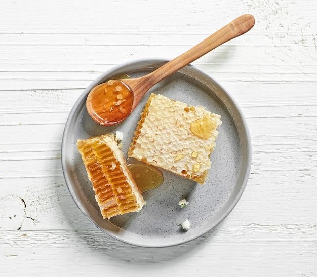 白い木製のテーブル、上面図に新鮮な蜂蜜の櫛のプレート