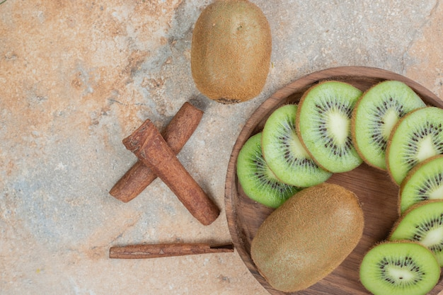 Тарелка свежих палочек киви и корицы на мраморной поверхности. фото высокого качества