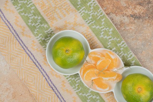 テーブルクロスの新鮮なマンダリンとセグメントのプレート。