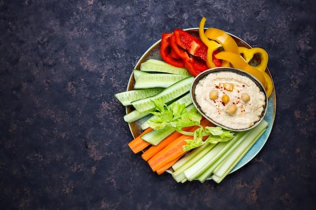 어두운 갈색 또는 콘크리트 표면에 후 머스와 신선한 유기농 야채 샐러드 접시
