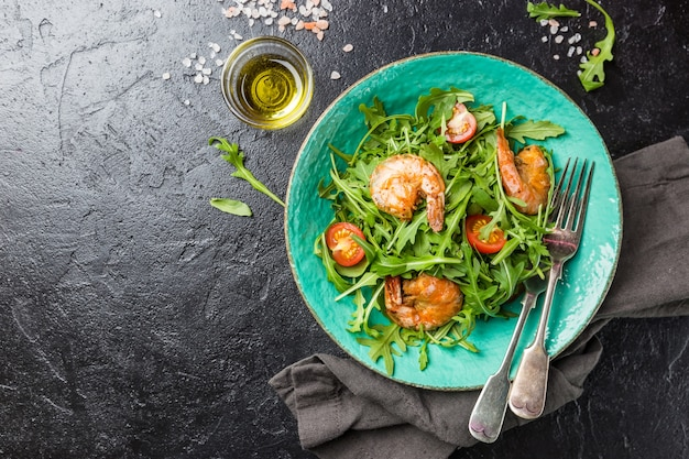 ルッコラまたはサラダロケット、エビ、トマトの新鮮なサラダのプレート、上面図。健康食品の概念。