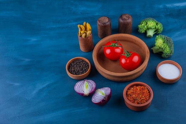 Тарелка из свежих помидоров, лука, брокколи и приправ на синей поверхности.