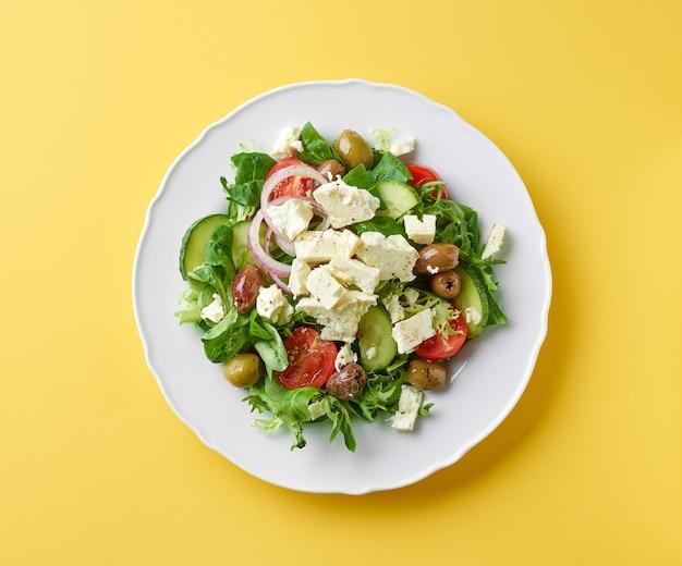 Тарелка греческого салата из свежих овощей с сыром фитаки на желтом фоне, вид сверху