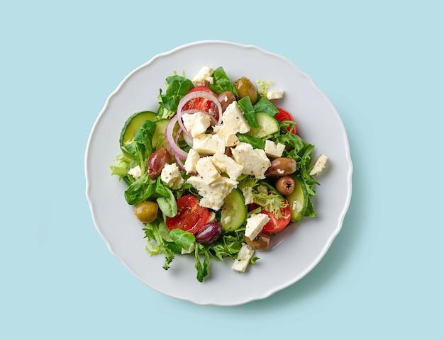 Тарелка салата из свежих овощей с греческим сыром на синем фоне, вид сверху