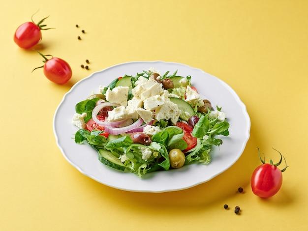 Тарелка салата из свежих овощей с греческим сыром на желтом фоне