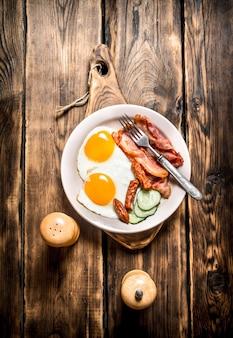 目玉焼き、ベーコン、きゅうり、スモークソーセージのプレート。木製のテーブルの上。