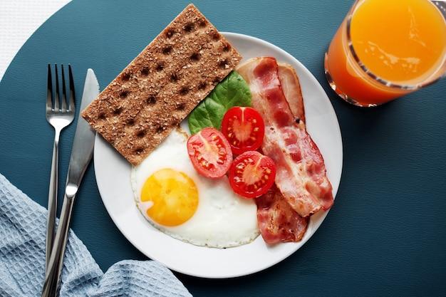 Тарелка яичница, бекон, помидоры, апельсиновый сок и тосты.