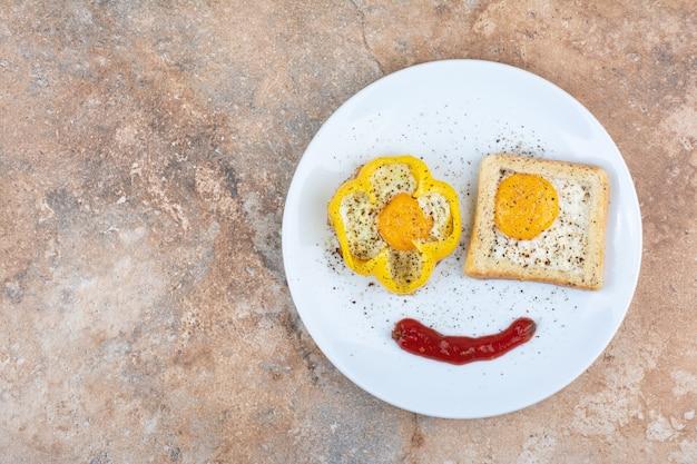 토스트와 대리석 표면에 향신료와 함께 튀긴 계란 접시
