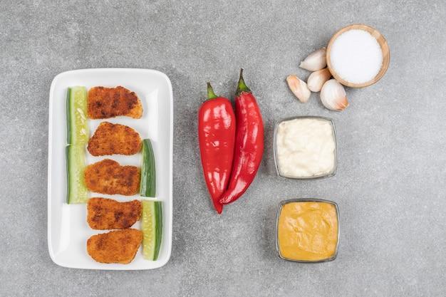 Тарелка жареных наггетсов и свежих овощей на мраморной поверхности