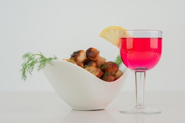 Тарелка жареного картофеля и стакан сока.