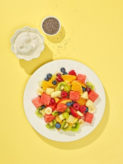 Тарелка фруктового салата на желтом фоне, вид сверху
