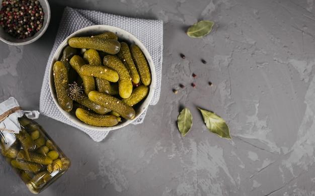 Тарелка корнишонов, маринованных огурцов на сером фоне бетона. чистая еда, концепция вегетарианской пищи. вид сверху с пространством для текста