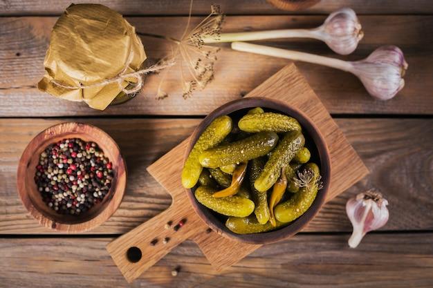 ガーキンのプレート、素朴な木製の背景にきゅうりのピクルス。きれいな食事、ベジタリアン料理のコンセプト