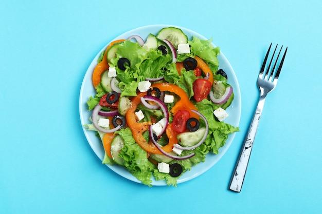 青い背景にギリシャ風サラダとフォークのプレート