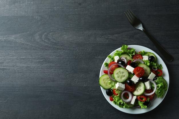暗い木製の背景にギリシャ風サラダとフォークのプレート