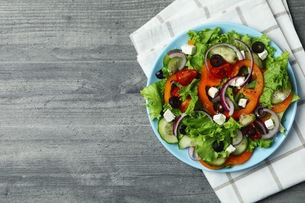 灰色のテクスチャ背景にギリシャ風サラダとキッチンタオルのプレート