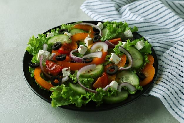 白いテクスチャ背景にギリシャ風サラダとキッチンタオルのプレート