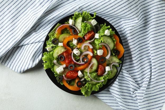 Тарелка греческого салата и кухонное полотенце на белом текстурированном